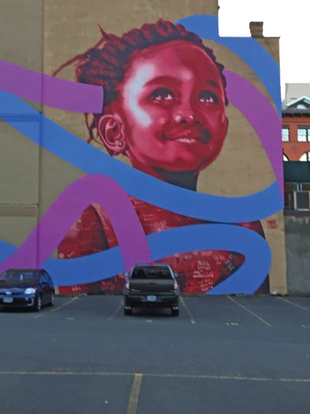 PORTLAND TRIBUNE: MICHAELA BANCUD - 'Under the Same Sky' is located on the Bishop's House in downtown Portland near Southwest Second  Avenue and Stark Street. Students from David Douglas High School and R.I.S.E. (Refugee & Immigrant Student Empowerment) created stencils and words in Arabic, Swahili, English and Somali about belonging and diversity.