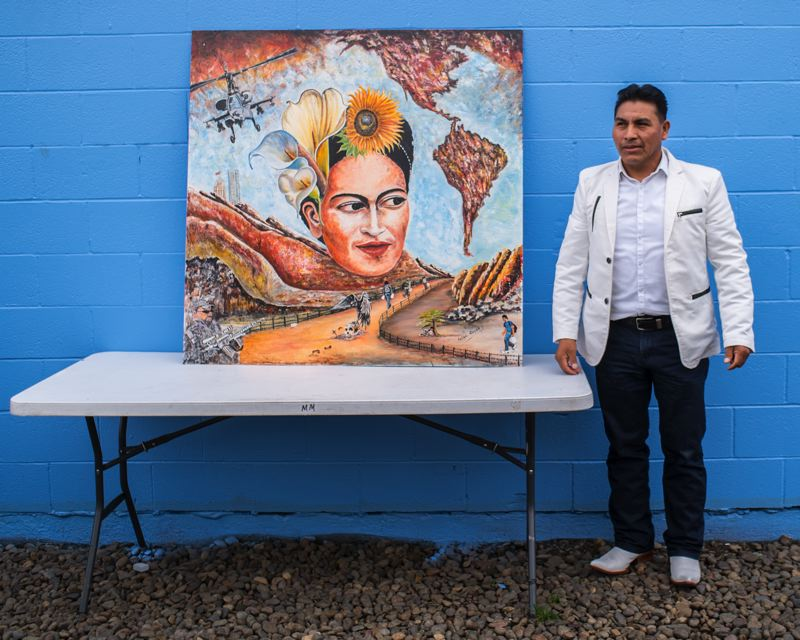 HILLSBORO TRIBUNE PHOTOS: CHASE ALLGOOD - Artist Felipe Gomez poses with his painting after unveiling it at the M&M Marketplace during the unveiling celebration of The Frida Project Saturday. Saturdays event was the first time that Gomez had ever shown his art in public.