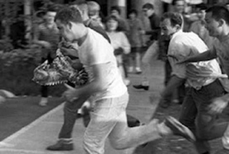 COURTESY PHOTO: WASHINGTON COUNTY HERITAGE ONLINE - A Pacific University student runs with Boxer under his arm during a Boxer toss, where opposing groups fought to possess the school mascot.