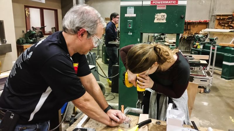 COURTESY PHOTO: TEAM SHOCKWAVE - Lead Mentor Alexandre Tenca works on the robot ball shooter system with Rachel Simedru (right).