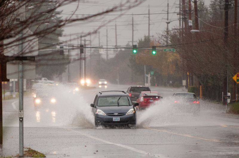FILE PHOTO - Cars negotiate a flooded Northeast Halsey Street in Fairview