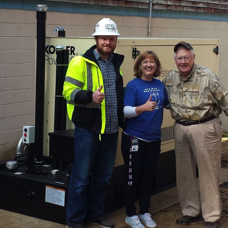 PHOTO COURTESY OF SAUVIE ISLAND ACADEMY - Jeremy Suhrstedt, an IES Electric employee, Sauvie Island Academy Director Darla Meeuwsen and George Ray, Joyce Miller Owens Charitable Foundation board member, stand with one of the donated generators outside of SIA. The generator at the school was installed Friday, Sept. 30.