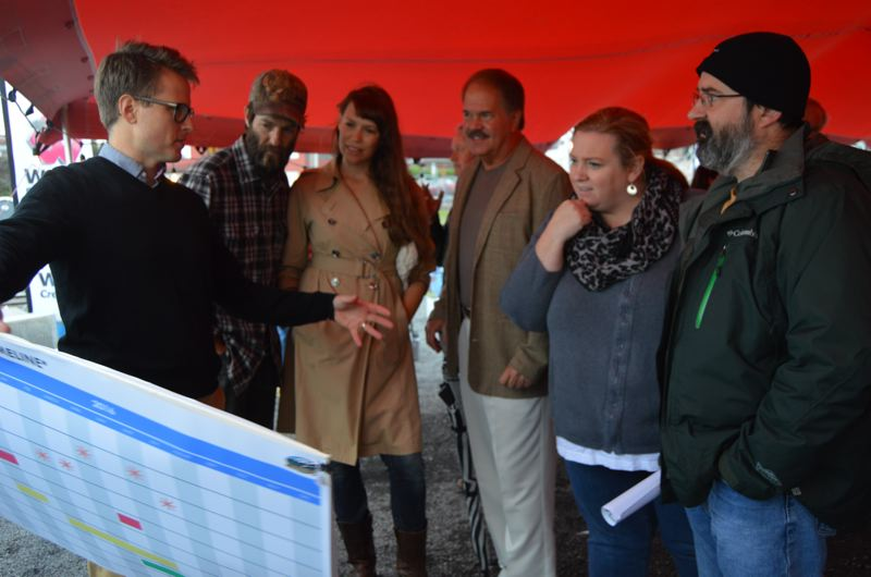 SPOTLIGHT PHOTO: NICOLE THILL - Design consultant Seth Otto holds up a display board while chatting with open house attendees Jeremy Furnish, Amanda Furnish, Randy Larson, Teressa Dillon an