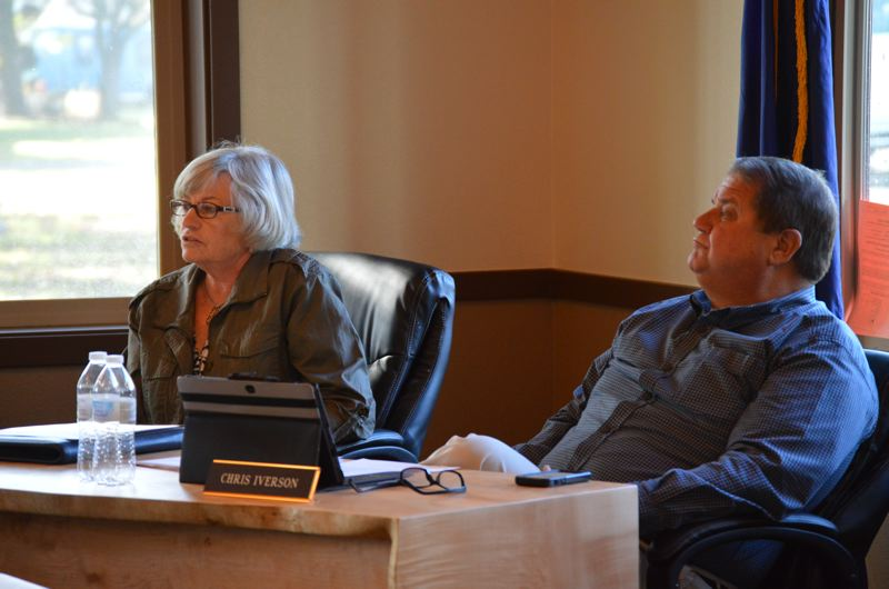 SPOTLIGHT PHOTO: COURTNEY VAUGHN - Port of St. Helens Commissioners Paulette Lichatowich (left) and Chris Iverson review a proposal from a land use firm that will cost the port more money to pursue rezone efforts at Port Westward. The request for more funds was ultimately approved.