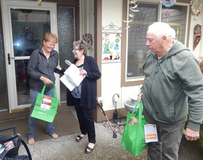 BARBARA SHERMAN - Judi Wandres (center) chats with Summerfield neighbor Judy Richter, who has just donated the bag of food held by Judi's husband J. Wandres for the Portland Food Project.