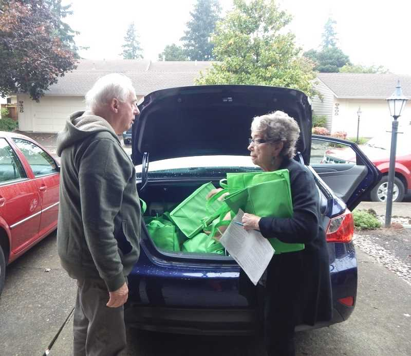 BARBARA SHERMAN - J. and Judi Wandres organize all the food bags they picked up Oct. 8 to take to a Portland Food Project collection center.