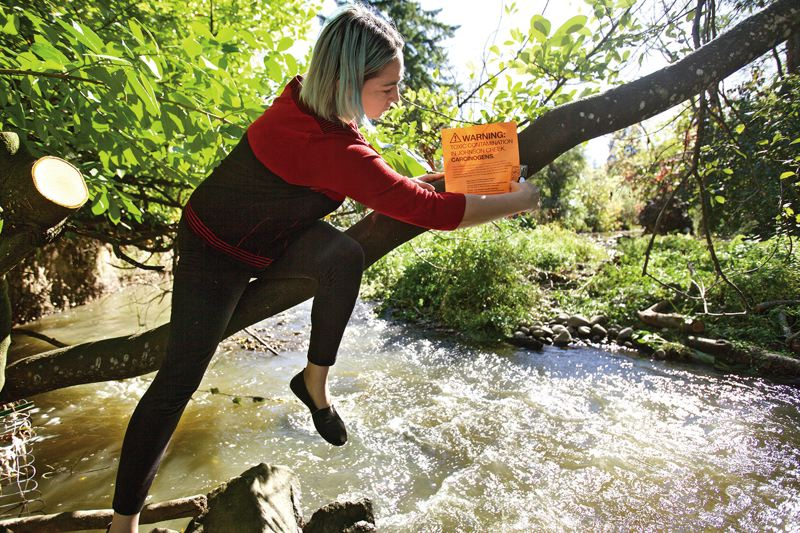 TRIBUNE PHOTO: JAIME VALDEZ - Julie Reardon posts her own warning signs alerting neighbors to PCBs found in Johnson Creek near David Ross's house. She lives 15 blocks from Precision Castparts, which is just upstream from the site.