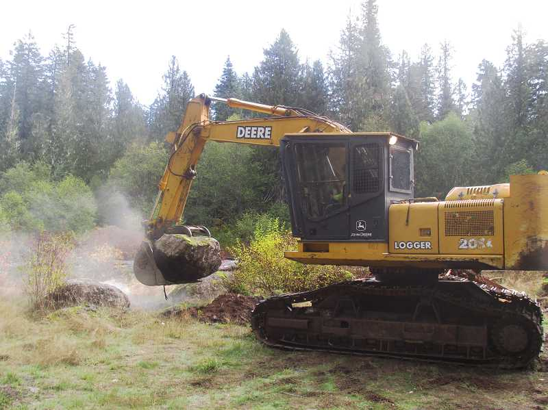 ESTACADA NEWS PHOTO: EMILY LINDSTRAND - A member of the OMalley Brothers team uses an excavator to move a boulder during a road decomission project in the Big Bottom wilderness area.