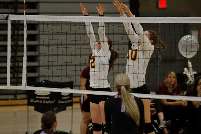 NEWS-TIMES PHOTO: WADE EVANSON - Forest Grove's front line jumps to block a spike during the Vikings' 3-1 loss to South Salem