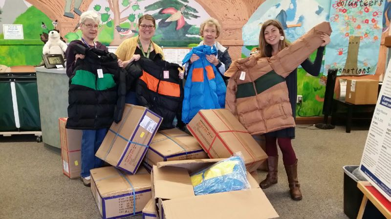 SUBMITTED PHOTO - Volunteer Joan Verry, from left, Danielle Schneider, administrative assistant, volunteer Sharon Newell and Katy Henkle, intern, unpack coats at the Wichita Center for Family & Community. The free coats were handed out on Oct. 20 as part of the Coats for Kids program.