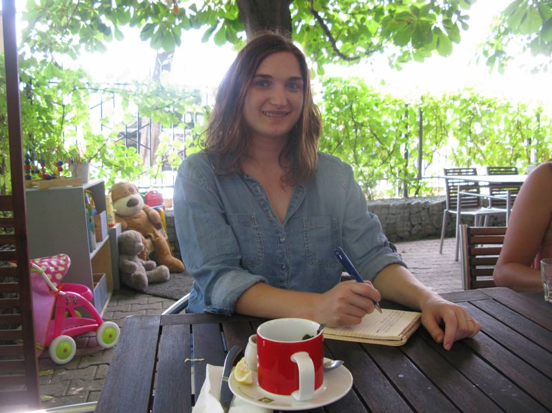 SUBMITTED PHOTO - Oregon City writer Hannah Gildea is caught on camera writing in her diary at a cafe in Prague. 'The Goulash Diaries' is the title of her Jan. 12 talk in Oregon City.