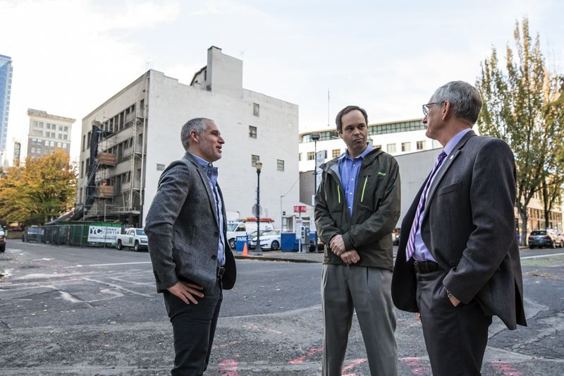 TRIBUNE PHOTO: JONATHAN HOUSE - Developer Tom Cody, Transition Projects executive director George Devendorf and Portland mayor Charlie Hales chat after a press conference to announce a new homeless shelter opening in Cody's empty buildings (pictured in back).