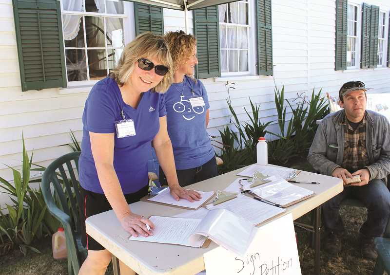 PEGGY SAVAGE - L-R: Lucy Allison-Pursley and Donna Russell collected petition signatures  for the Molalla Aquatic Center at the Molalla Apple Fesitival in  September.