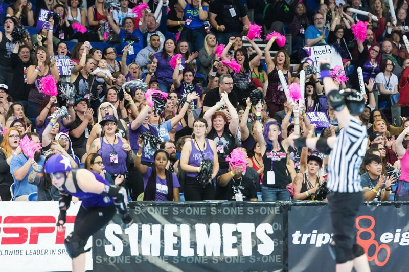 TRIBUNE PHOTO: CHRISTOPHER OERTELL - Rose City Rollers fans at Memorial Coliseum go wild as the team scores big down the stretch to defeat Gotham in the international championship roller derby match.