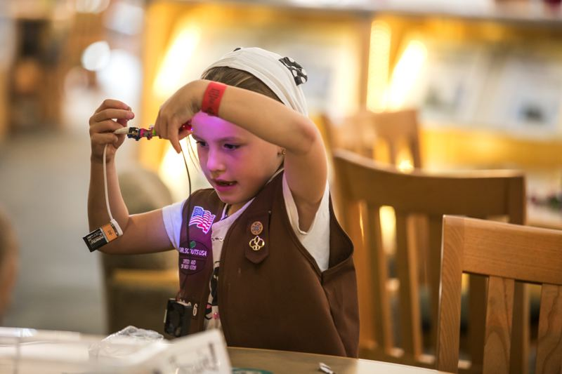 TIMES PHOTO: JONATHAN HOUSE - Adeline Lund makes a LED bulb light up at a Makerspace event at the Tualatin Library.