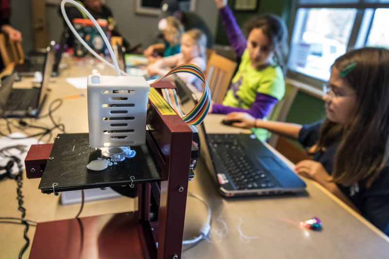 TIMES PHOTO: JONATHAN HOUSE - Children use a 3D printer during a Makerspace event at the Tualatin Library.