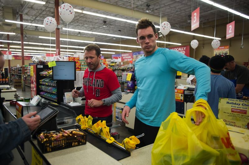 OUTLOOK PHOTO: JOSH KULLA - Portland Trail Blazer guard Pat Connaughton (right) bags groceries for Gresham Mayor Shane Bemis Monday during the annual Fill-A-Bag food drive at the Gresham Grocery Outlet supermarket.