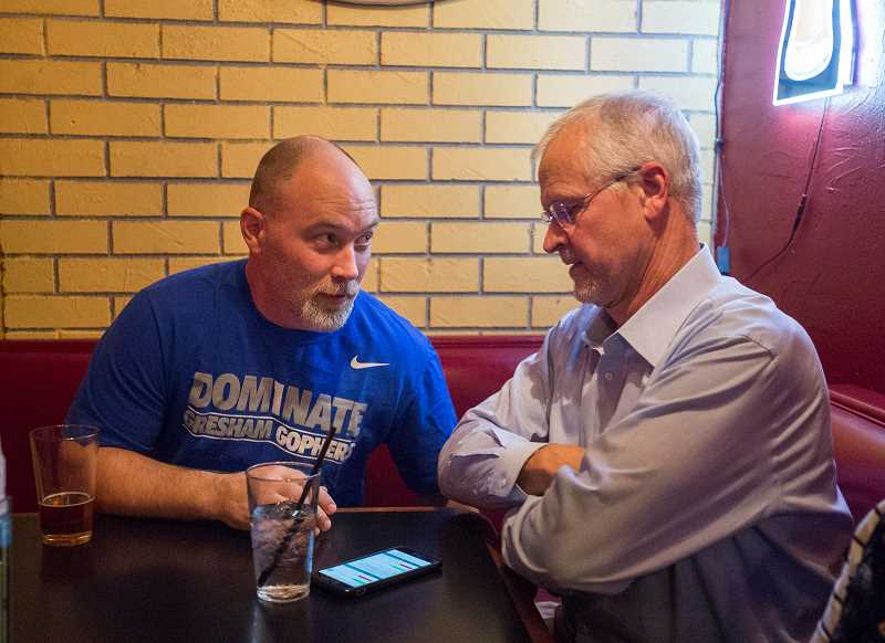 OUTLOOK PHOTO: JOSH KULLA - Gresham-Barlow School District Bond Chairman Jason Dugan chats Tuesday night with district superintendent Jim Schlachter at an election party at Uly's in downtown Gresham.