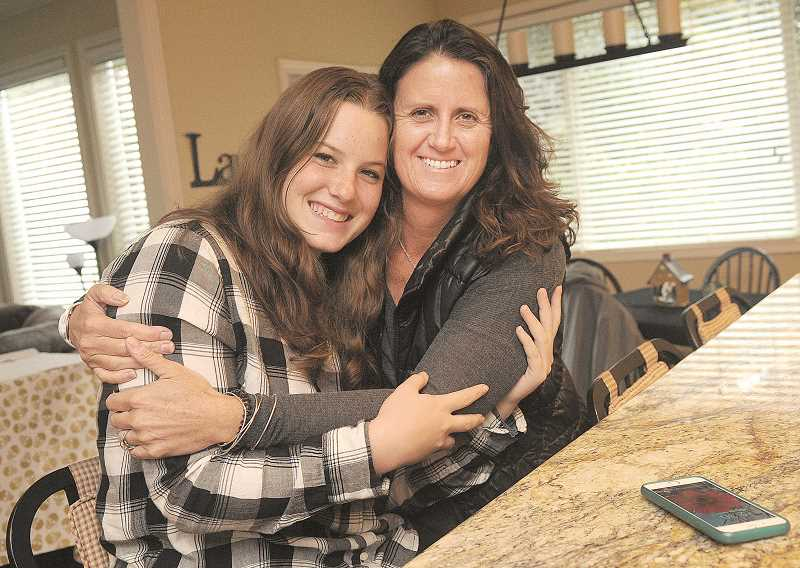REVIEW PHOTO: VERN UYETAKE - Lolly Pasotti gets a big hug from Molly Mullen, her host mom in Lake Oswego. Mullen says Lolly is already helping her make lasagna and bruschetta.
