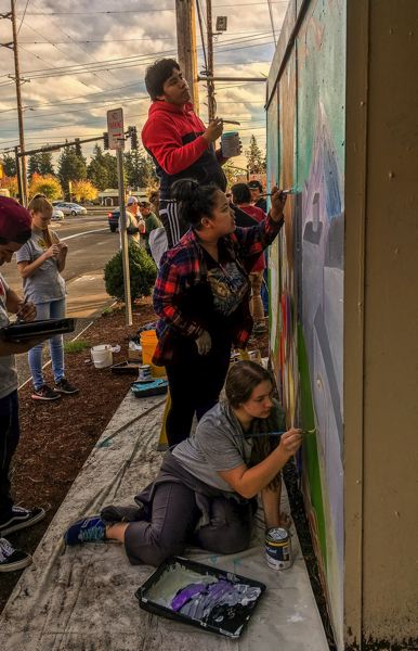 OUTLOOK PHOTO: JOSH KULLA - Youth Advisory Committee members, including Gerardo Miguel de la Cruz, top, and Rebekah Burns, bottom, help paint a mural dedicated to slain teenager Larnell Bruce Friday at the Rockwood 7-Eleven where Bruce was murdered.