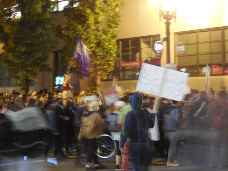 PAMPLIN MEDIA GROUP: JOSEPH GALLIVAN - Anti-Trump protesters crossed the Broadway Bridge around 9.45pm Thursday and paused at the corner of Lovejoy St. and NW 13th Ave. Windows at the Bank of America ATM room were broken. The crowd included a woman on stilts with a purple peace flag led a chant of 'peaceful protest,' which was taken up by the majority of the crowd, who then headed south toward downtown.