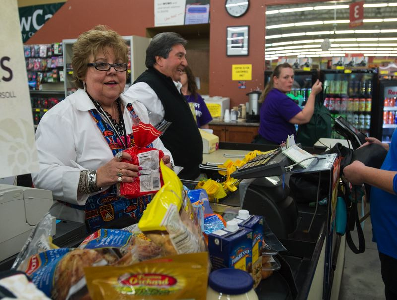 OUTLOOK PHOTO: JOSH KULLA - Bess Wills of Gresham Ford works the checkstand at Grocery Outlet Monday along with Bob Avila as part of a Snowcap fundraiser for the Fill-A-Bag food drive.