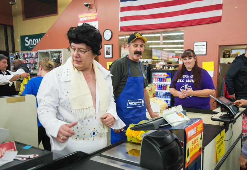 OUTLOOK PHOTO: JOSH KULLA - Larry Schwartz, branch manager at Gresham Riverview Community Bank, works a checkstand at Grocery Outlet along with Jim Thurber of reality TV show 'Goldrush' Monday during a fundraiser for Snowcap's Fill-A-Bag food drive.