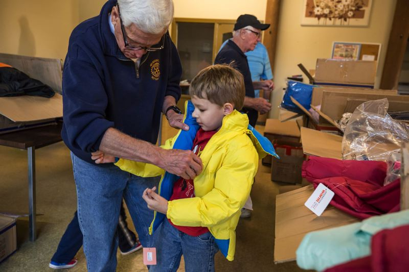 TIMES FILE PHOTO - A boy tries on a winter coat at a clothing giveaway event that Community Partners for Affordable Housing held this fall in Beaverton.