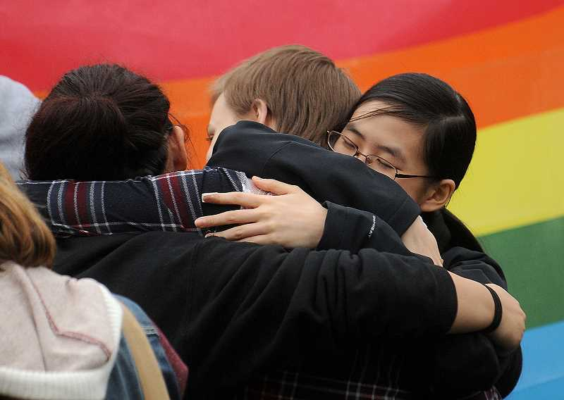 TIDINGS PHOTO: VERN UYETAKE - Students embrace during Monday's walkout.