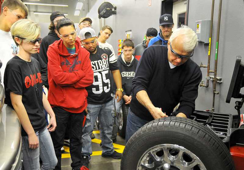 GRAPHIC PHOTO: SETH GORDON - Clackamas Community College instructor Les Blahuta shows Newberg High School students how to balance a tire at the World of Speed auto shop in Wilsonville.