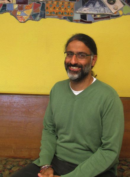 OUTLOOK PHOTO - Centennial Park Principal Ajai Huja sits in an old church pew in the lobby of Centennial Park School.