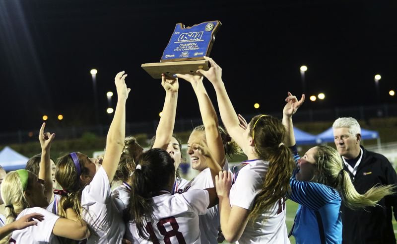 DAN BROOD - All of the Lady Bowmen reach for the state championship trophy following their 2-1 win over Sunset in Saturday's state title match.