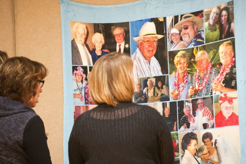 OUTLOOK PHOTO: JOSH KULLA - Memories of Bill adorned the entire banquet room where his birthday party was held. Here, family members enjoy a display of photos of Bill taken through the years.