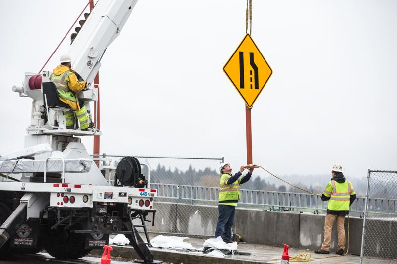 TRIBUNE PHOTO: JONATHAN HOUSE - Subcontractors place the merging sign eastbound near the west intersection of the bridge.