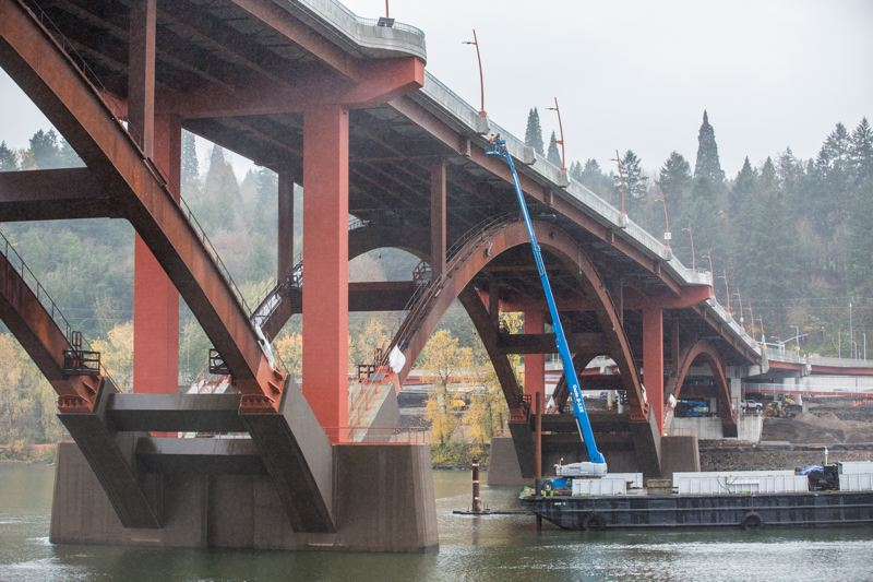 TRIBUNE PHOTO: JONATHAN HOUSE - Crew finish up the final touches on the new Sellwood Bridge, a steel deck arch bridge and the busiest two-lane bridge in the state.