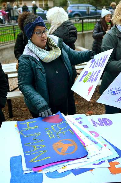 REVIEW PHOTO: VERN UYETAKE - Sasha Watson of Lake Oswego picks out a sign to carry inFriday's walk to promote peace, love and diversity.