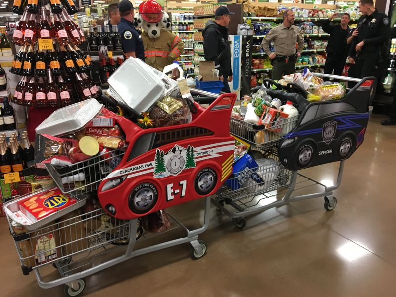 SUBMITTED PHOTO - Clackamas Fire dog mascot Sparky oversees the groceries valued at $885, which were donated to the Clackamas Service Center.