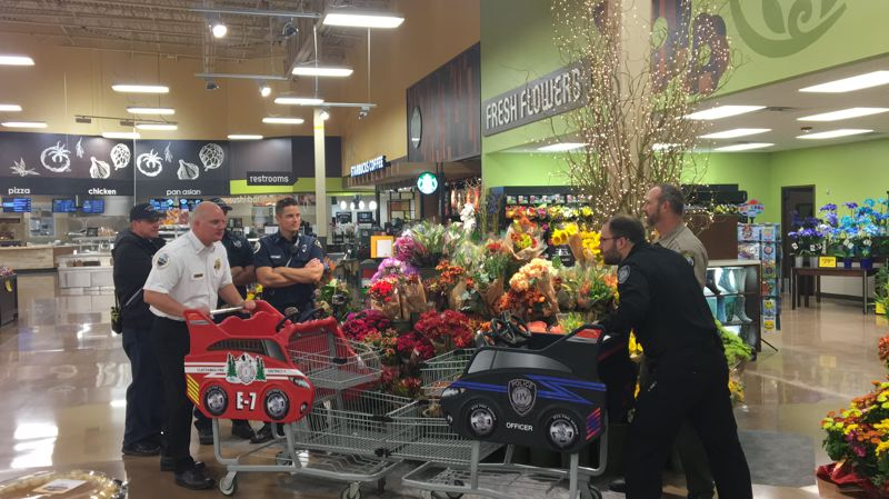 SUBMITTED PHOTO - Clackamas Fire Chief Fred Charlton (left) faces off against the representatives for the Clackamas County Sheriff's Office prior to the charity shopping challenge.