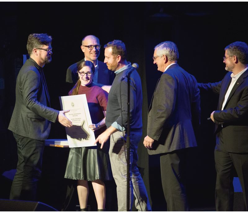 PAMPLIN MEDIA GROUP: ADAM WICKHAM - Jennifer Dzienis, (red sweater) a partner at Works Progress Architecture since January 2016, accepting on of four awards which W.PA won at the AIA Portland annual awards Nov 17, 2016. On the far right is Mayor Charlie Hales, a champion of local architecture who enjoys giving his annual Mayors Awards.