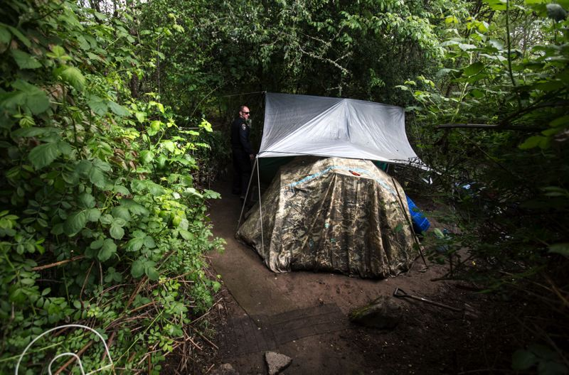 FILE - Tigard Police Officer Brian Orth checks a homeless tent near a walking trail earlier this year. Homelessness in the Tigard area has attracted the city's attention.