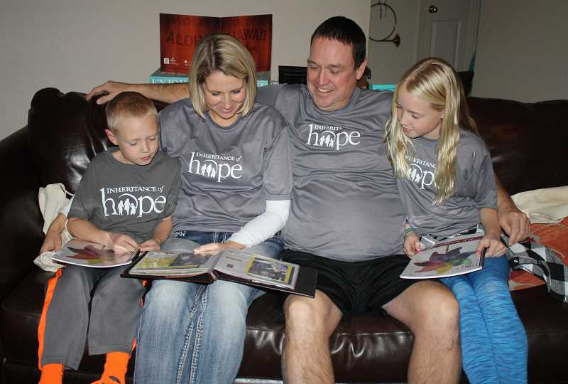 HOLLY SCHOLZ/CENTRAL OREGONIAN   - The Prineville O'Gorman family looks at a scrapbook with photos of their recent Legacy Retreat to New York City through the Inheritance of Hope organization. Pictured left to right: Graeme, Jennifer, Pat and Merritt.