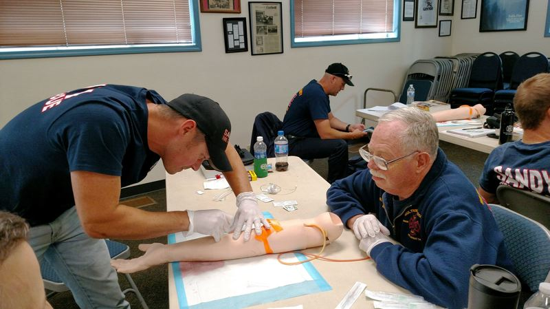 CONTRIBUTED PHOTO - Sandy volunteer firefighter Shawn Crawford, left, inserts an IV line on a training dummy as Duane Redfield, 66, watches. Redfield has been with Corbett Fire for 36 years.