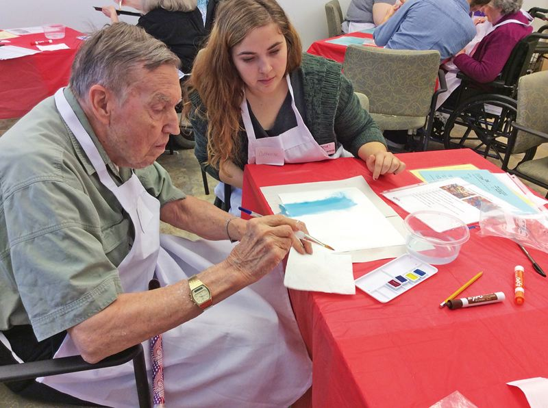 SUBMITTED PHOTO - A Rose Villa artist begins a watercolor project, watched over by volunteer Catherine Wiese, an undergraduate at Marylhurst University.