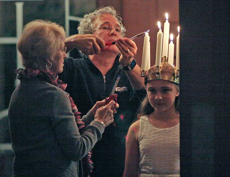 PAMPLIN MEDIA GROUP - ISing Artistic Director/Conductor Stephen Galvan, center, lights the candles on Maddie Green's crown for her solo as Sankta Lucia during a dress rehearsal for ISing's 'Mus(e)cology' for two performances held at Portland's St. Peter Catholic Church and Beaverton's Bethel Congregational United Church earlier this month.