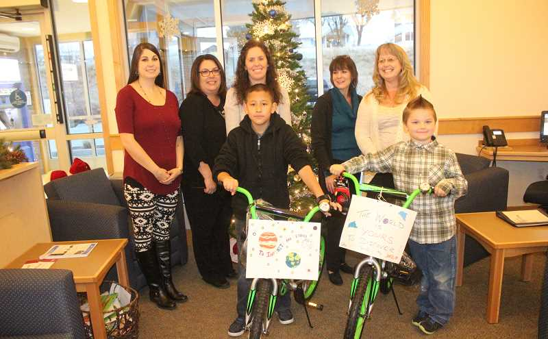 SUSAN MATHENY/MADRAS PIONEER -  The staff at Mid Oregon Credit Union in Madras assembled the bicycles, which were presented to students Adrian Hernandez, on left, 11, from Madras Elementary, and Brayden Greenhalgh, 7, from Buff Elementary.