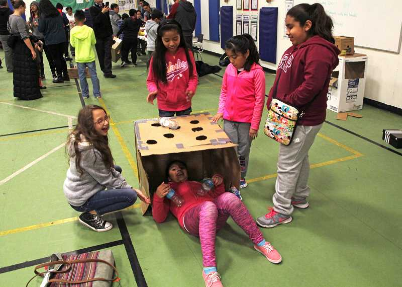 JULIA COMNES - Fifth-grader Irene Rodriguez (left) made a version of Whac-a-Mole out of a cardboard box and plastic water bottles.