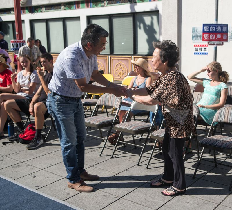 COURTESY PHOTOS - Mrs. May Oka, the former owner of Wong Laundry and one of eight Wong children, hands Hongcheng Zhao the key to the building at a Chinatown Saturday Performance he organized for the community.
