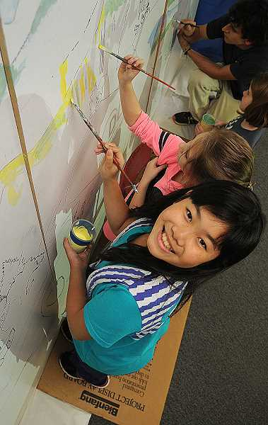 TIDINGS PHOTO: VERN UYETAKE - Sarina Tsai works on a murual for Stafford Primary that depicts the life cycle of salmon.