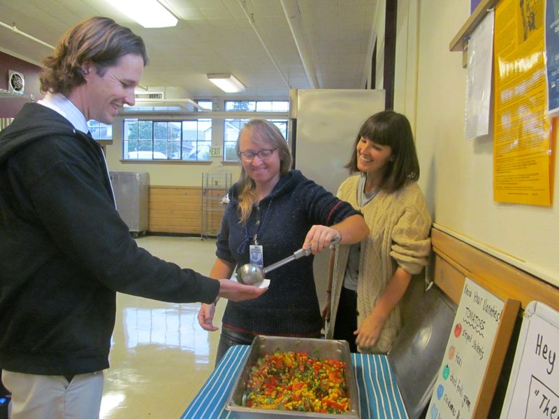 PHOTO BY ELLEN SPITALERI - Noah Hurd, principal at New Urban High School, gets a serving of corn and tomato salad from Brooke Hieserich, education director at Schoolyard Farms, while Courtney Leeds, executive director of Schoolyard Farms looks on.