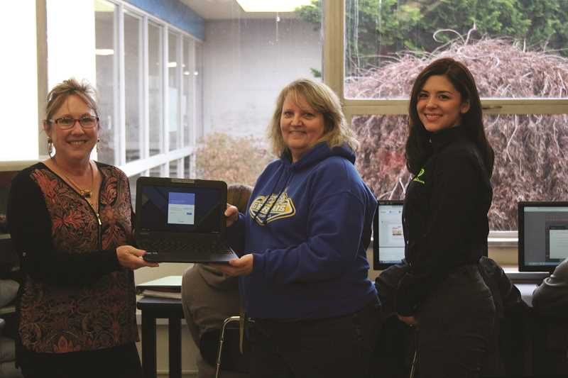 PHIL HAWKINS - From left, DataVision Cooperative President-General Manager Renee Willer, Gervais High School counselor Myra Adams and DataVision marketing and sales supervisor Marissa Gainer display one of the Google Chromebooks Gervais High School will be able to purchase with their $5,000 grant from the Foundation for Rural Service.